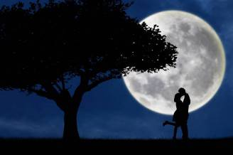 Couple kissing by a tree on blue full moon silhouette