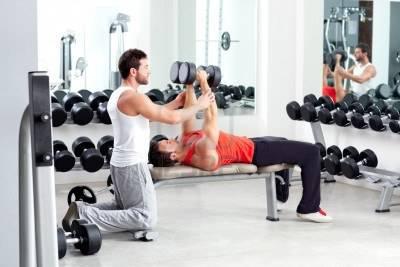 11982236-palestra-uomo-personal-trainer-con-attrezzature-allenamento-con-i-pesi