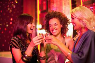 Friends toasting shot glasses in nightclub. Image shot 2010. Exact date unknown.