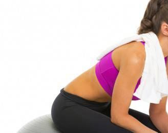 Closeup on fitness woman sitting on fitness ball