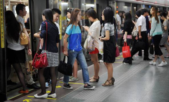 Women queue up to board a subway train i