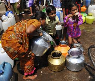 An Indian woman fills a pot with drinkin