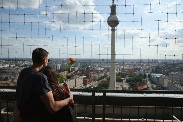 BERLIN, GERMANY - JUNE 18:  A young couple standing on the rooftop terrace of a hotel look out at the broadcast tower at Alexanderplatz on June 18, 2014 in Berlin, Germany. Alexanderplatz, a crossing point of tourists, commuters, shoppers, lovers, artists, bums and petty criminals, was built from the rubble of World War II by the communist authorities of former East Germany and today is the nexus of the reunified city.  (Photo by Sean Gallup/Getty Images)