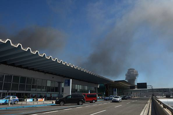Smoke is seen over Rome's Fiumicino international airport where a fire broke out overnight on May 7, 2015. No serious injuries were reported as a result of a blaze which took hold around 5:00 am (0300 GMT) in terminal three of the Italian capital's main hub, which is located on the coast around 30km (20 miles) west of the city. Several airport employees were suffering from the effects of smoke inhalation, airport officials said.  AFP PHOTO / TIZIANA FABI        (Photo credit should read TIZIANA FABI/AFP/Getty Images)