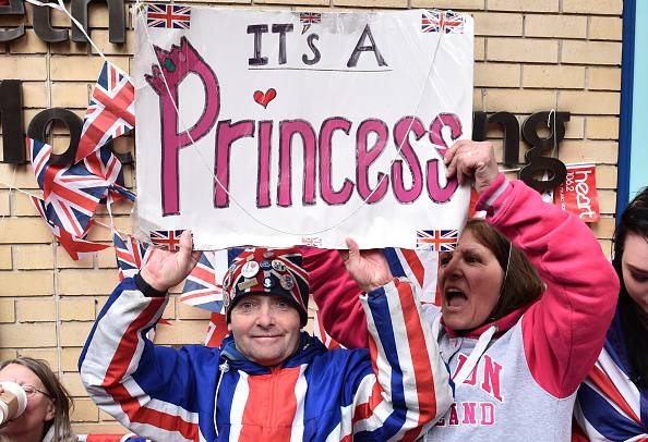 Royal fans celebrate outside the Lindo wing at St Mary's hospital in central London, on May 2, 2015 after the news is passed that Catherine, Duchess of Cambridge and Prince William's second child, a daughter, was born. The Duchess of Cambridge was safely delivered of a daughter weighing 8lbs 3oz, Kensington Palace announced. AFP PHOTO / LEON NEAL        (Photo credit should read LEON NEAL/AFP/Getty Images)