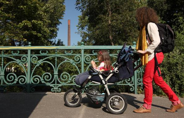 BERLIN, GERMANY - SEPTEMBER 16:  A mother pushes her three-year-old daughter in a stroller on September 16, 2012 in Berlin, Germany. Germany is currently debating the introduction of a nation-wide home child care subsidy (Betreuungsgeld), which would provide parents of one to three-year-old children the option of receiving EUR 150 (196.91 USD) a month to care for the child at home rather than sending him or her to a daycare center. Critics argue it would prevent the integration of children of recent immigrants into German society.  (Photo by Adam Berry/Getty Images)