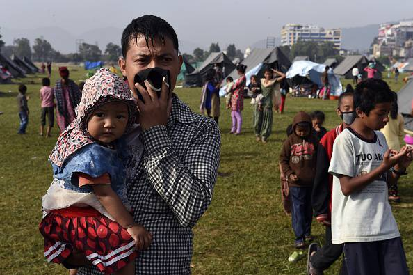 A Nepalese man holds a child in his arms as he watches other stand in line to receive childrens supplies handed out by volunteers at a camp in Kathmandu on May 5, 2015, which was set up for people left homeless after an April 25 earthquake that hit Nepal. It is estimated that tens of thousands were left homeless by the disaster.   AFP PHOTO/ROBERTO SCHMIDT        (Photo credit should read ROBERTO SCHMIDT/AFP/Getty Images)