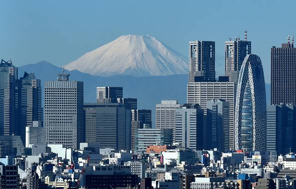 Japan's highest mountain, Mount Fuji (C) is seen behind the skyline of the Shinjuku area of Tokyo on December 6, 2014. Tokyo stocks closed at a seven-year high on December 5 -- extending their winning streak for a sixth straight day -- as a falling yen and oil prices continue to boost investor spirit.  AFP PHOTO / KAZUHIRO NOGI        (Photo credit should read KAZUHIRO NOGI/AFP/Getty Images)