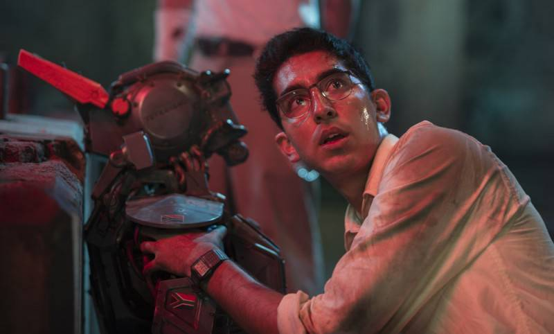 Deon (Dev Patel) boots up Chappie (Sharlto Copley) in Columbia Pictures' action-adventure CHAPPIE.