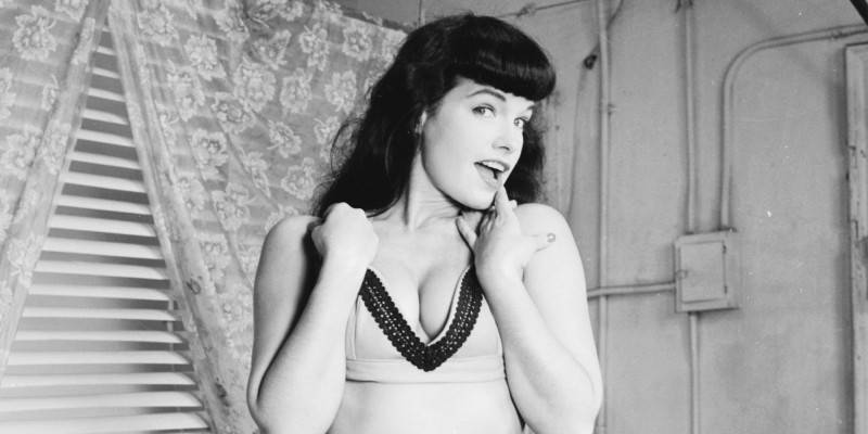 American pin-up Bettie Page, Playboy playmate of the month for January 1955 poses for a glamour shoot, 1950s. (Photo by Weegee(Arthur Fellig)/International Center of Photography/Getty Images)