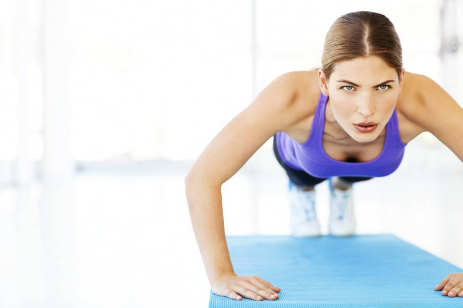 Woman Looking Away While Performing Push-Ups On Exercise Mat