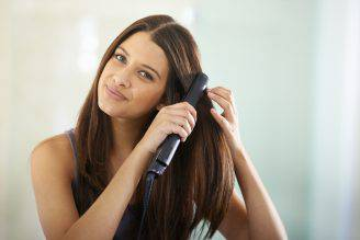 Portrait of an attractive woman straightening her hair with a flat ironhttp://195.154.178.81/DATA/i_collage/pi/shoots/783430.jpg