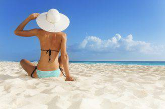 Tanned young girl sitting on the beach wearing blue striped swimwear and big hat