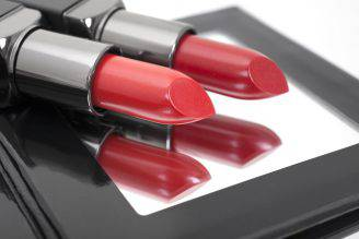 Two trendy red lipstick shades on compact mirror.