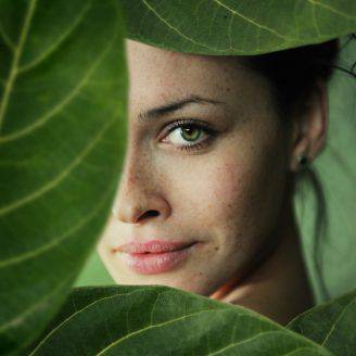 a close-up portrait of young beautiful women in leaf frame