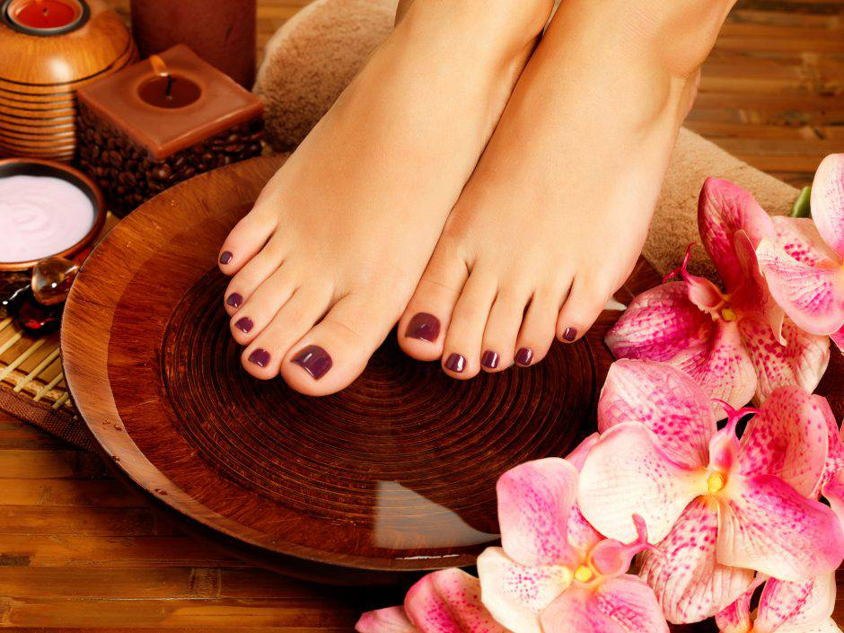 Closeup photo of a female feet at spa salon on pedicure procedure. Legs care concept