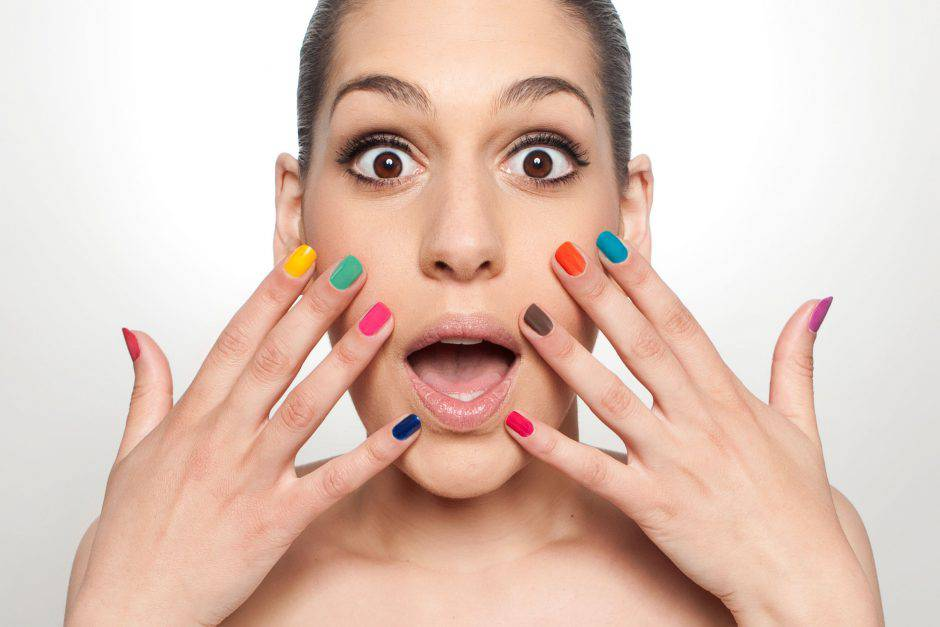 Surprised young woman with different colored nails