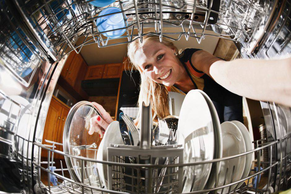 Seen, unusually, from inside the dishwasher drum, a pretty blonde smiles as she loads dishes.