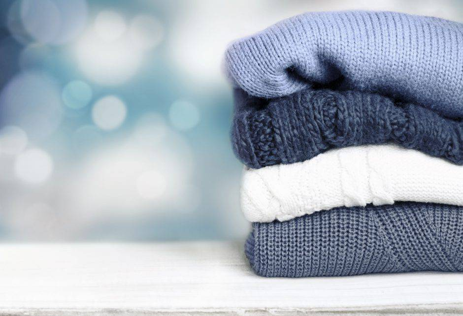 Stack pile of knitted winter clothes on wooden background empty space for text.Cozy autumn fall textile.
