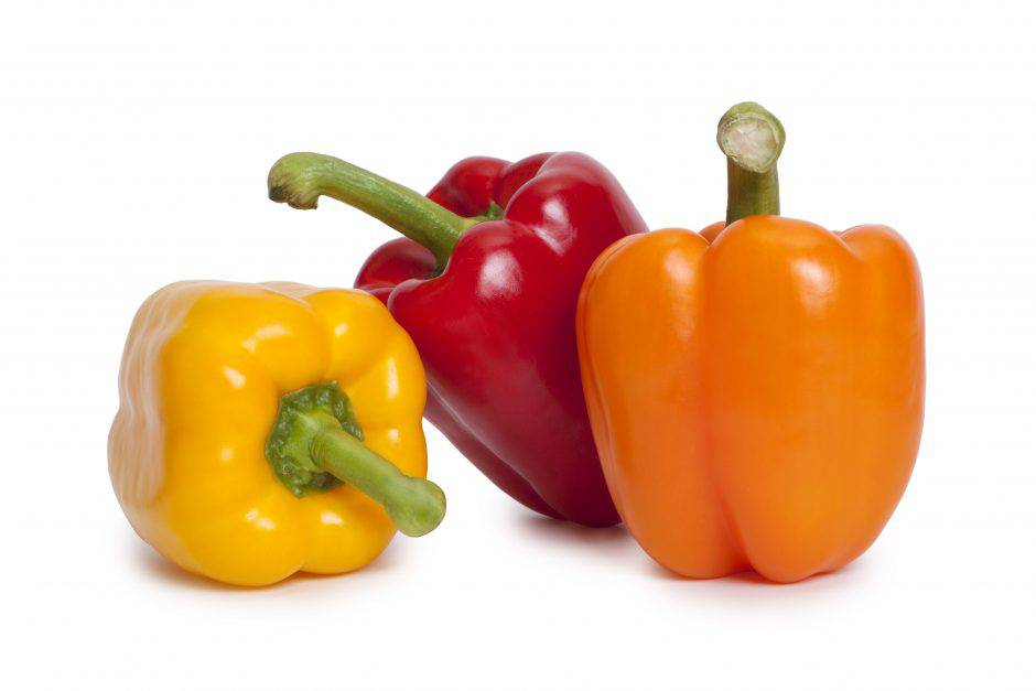 Three different coloured peppers arranged in a group.