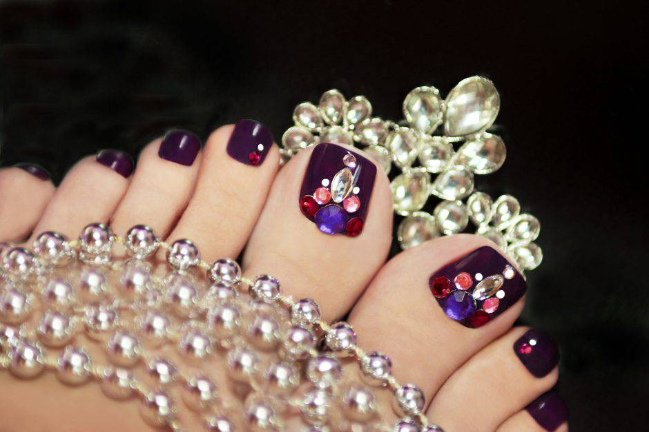 Holiday elegant purple pedicure with rhinestones on a black background with jewelry.