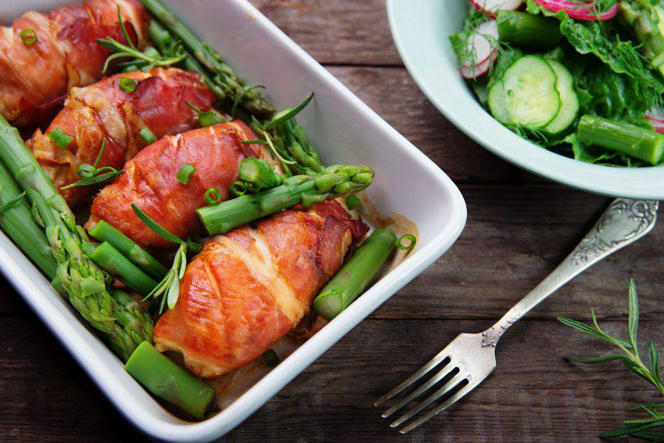 chicken breast wrapped in parma ham with green asparagus in ceramic dish