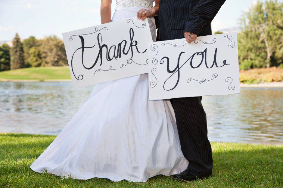 Young Wedding Couple Holding Thank You Signs. Focus is best on the signs.