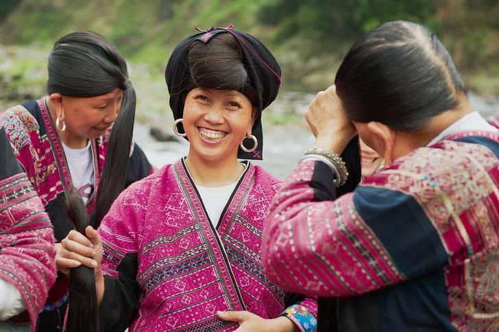 LONGJI, CINA \u2013 6 MAGGIO 2009 Le donne non identificate spazzolano e  intrecciano i capelli in Longji, Cina. Le donne di Red Yao che vivono nel  villaggio di
