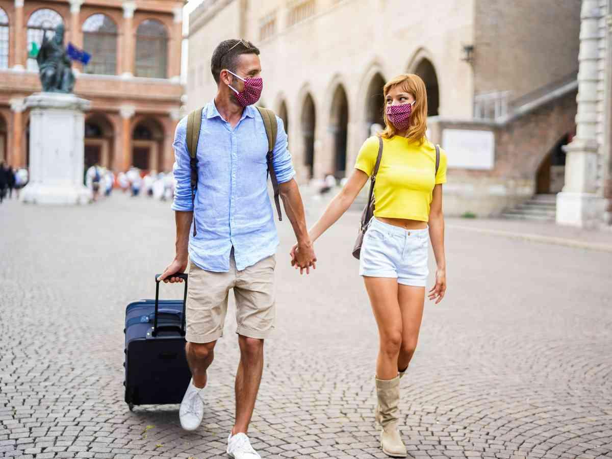 coppia con mascherina e valigia