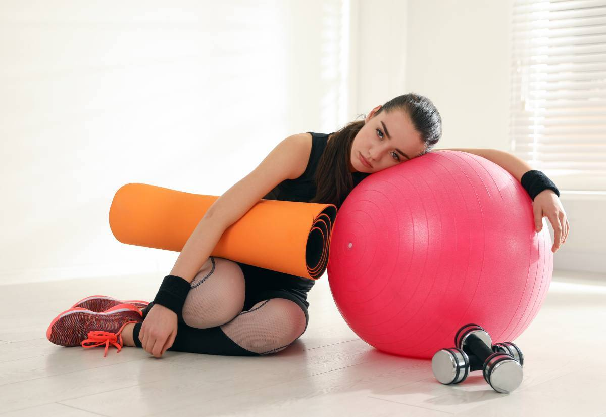 Donna pigra con attrezzi da fitness