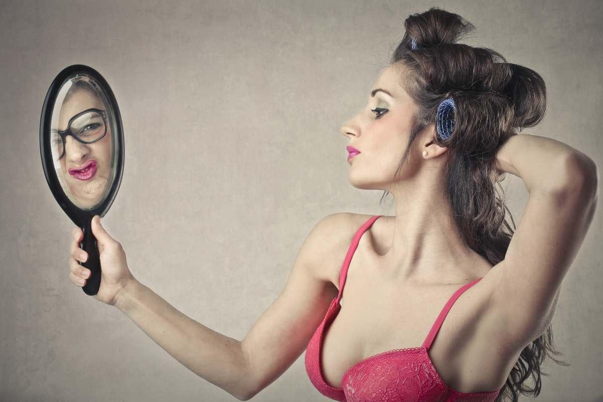 ragazza allo specchio che si vede diversa