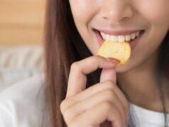 Giovane donna che mangia patatina fritta