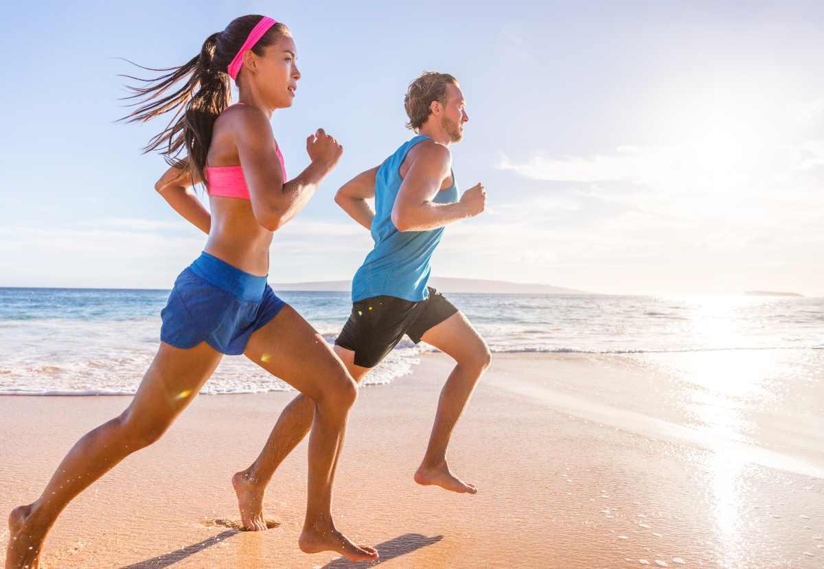 Uomo e donna che corrono in spiaggia