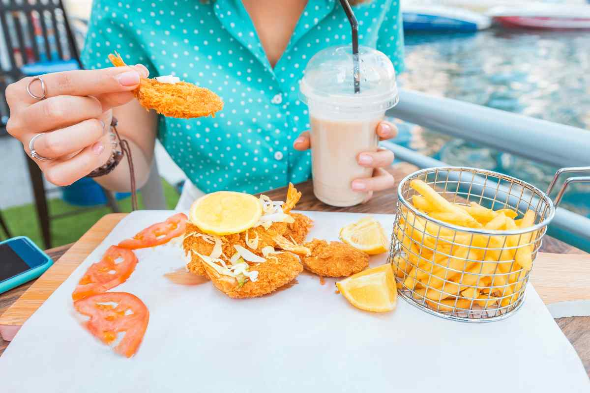Donna che mangia cibo fritto