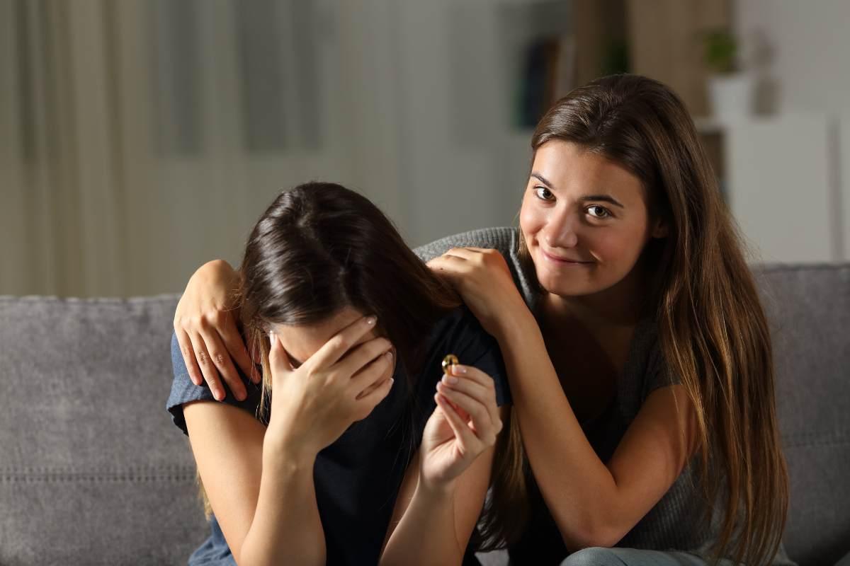 Donna che sorride con amica che piange