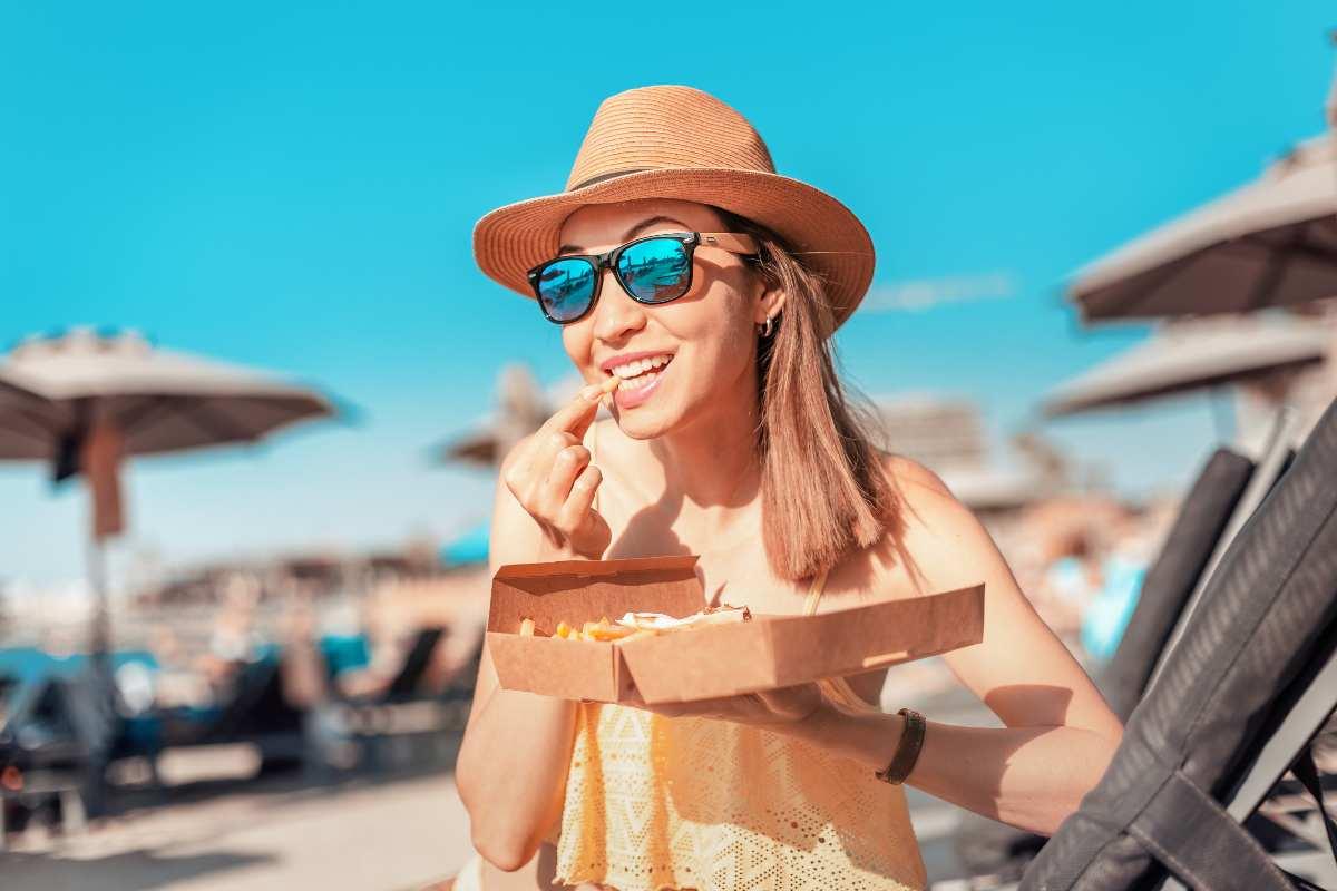 Donna con junk food al mare