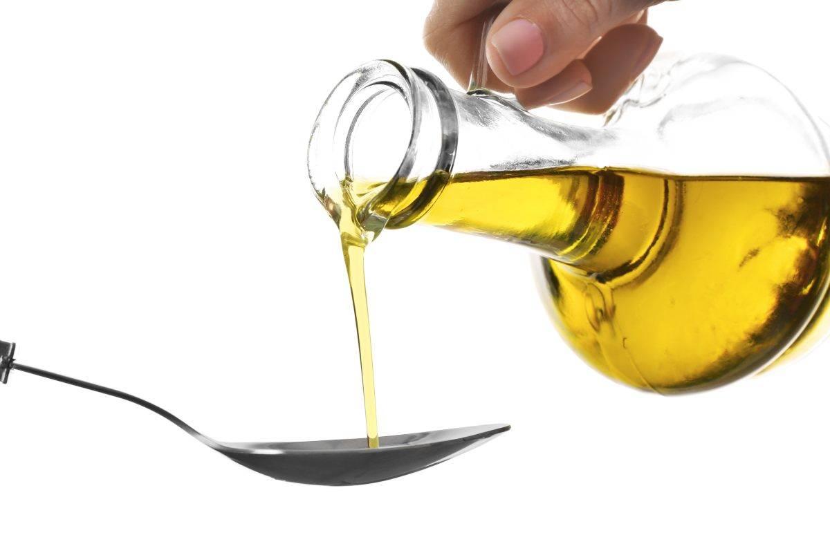 donna che versa olio d'oliva su cucchiaio