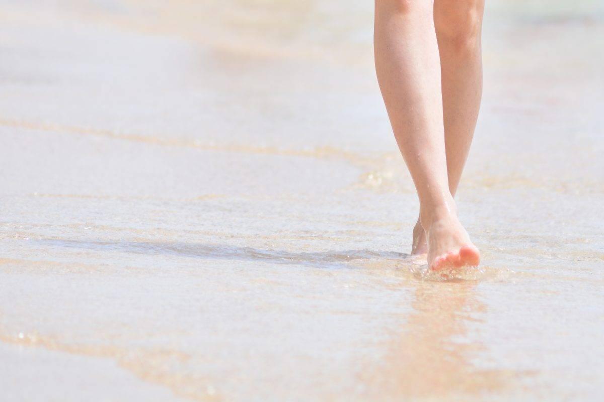 donna a piedi nudi sulla spiaggia