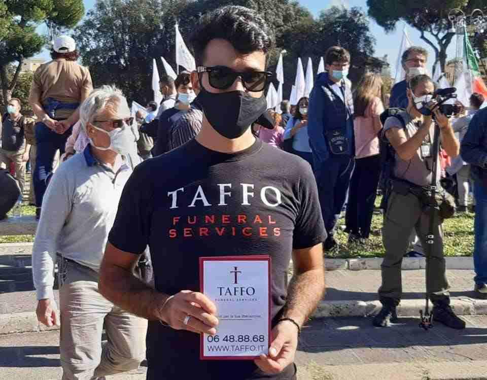 manifestazione 'no mask' ragazzo distribuisce volantini onoranze funebri
