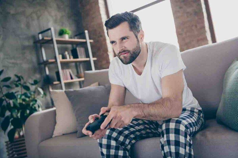 uomo seduto sul divano a giocare