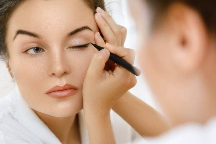 donna che applica l'eyeliner