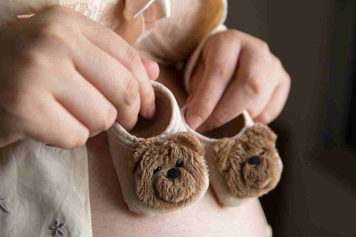 donna incinta con pantofoline da bimbo