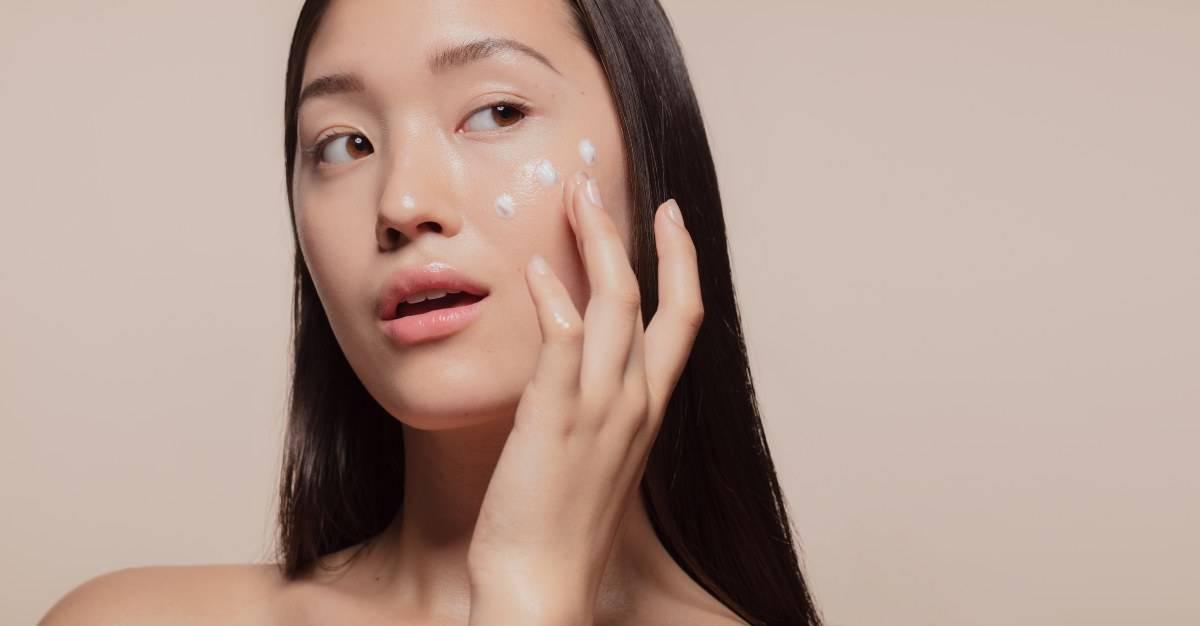 donna asiatica mette crema viso