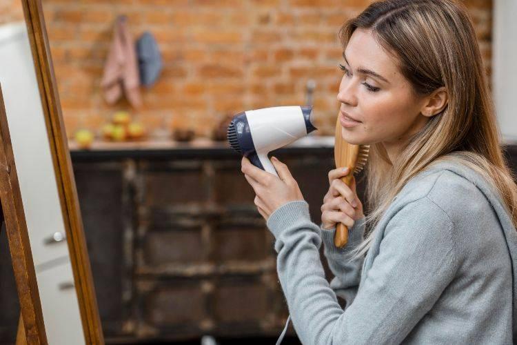 donna che si asciuga i capelli con il phon