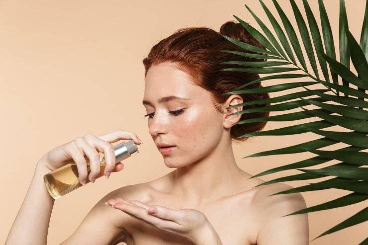 donna applica olio su pelle