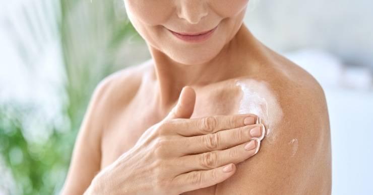 donna che applica crema corpo