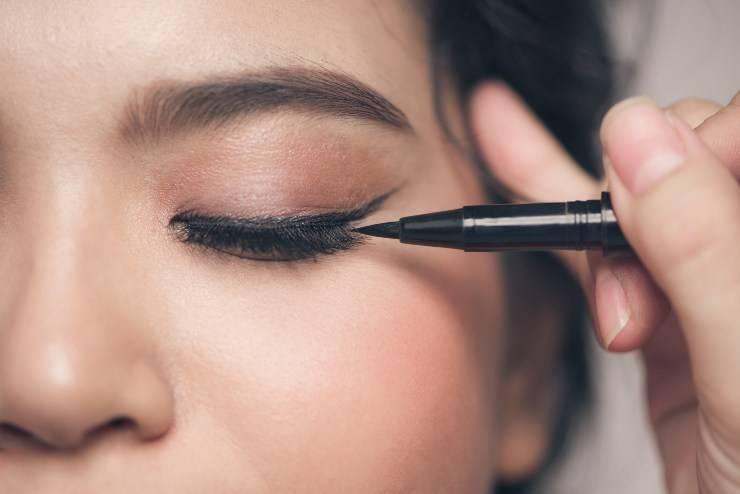 donna che applica eyeliner
