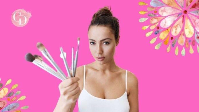 donna che tiene pennelli per il trucco in mano