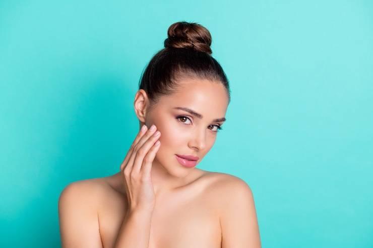 donna che applica crema idratante viso