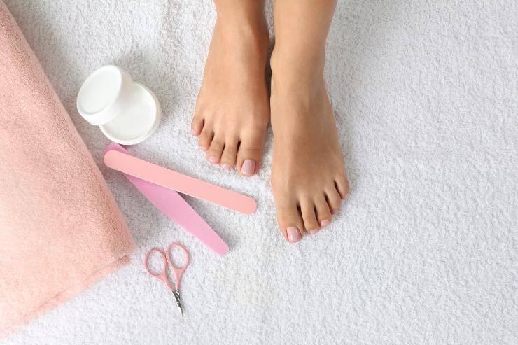piedi donna con strumenti pedicure so fondo grigio